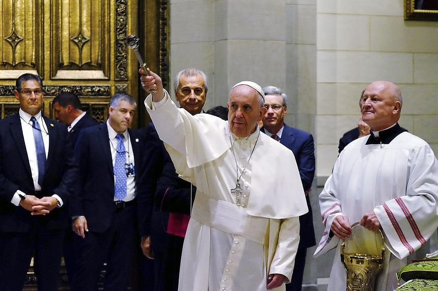Pope Francis (centre) sprinkles holy water as he enters St. Patrick's Cathedral to celebrate evening prayers in New York, on Sept 24, 2015.