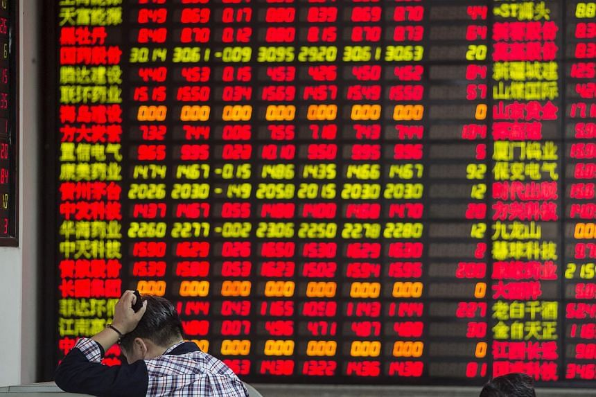 A man stands in front of an electronic board displaying share prices at a securities exchange house in Shanghai, China.