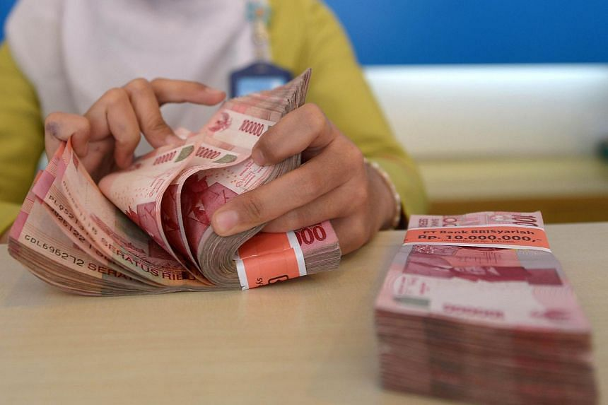 A bank employee counting Indonesian rupiah bank notes in Jakarta on Aug 25, 2015.