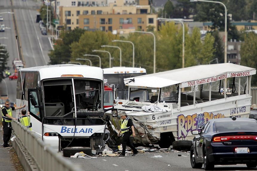 Investigators are pictured at the scene of a crash between a Ride the Ducks vehicle and a charter bus on the Aurora Bridge in Seattle, Washington on Sept 24, 2015.