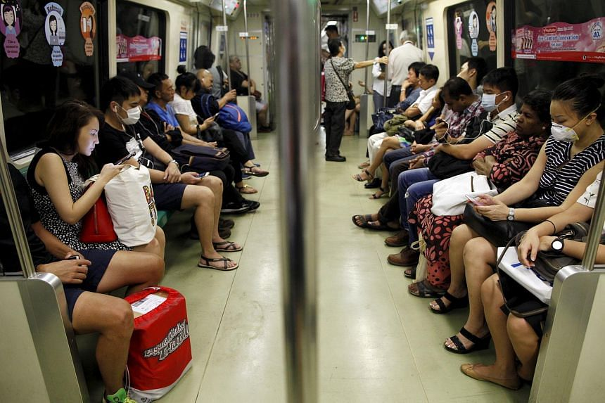 People wearing masks on the train during the morning commute in Singapore on Sept 25, 2015.