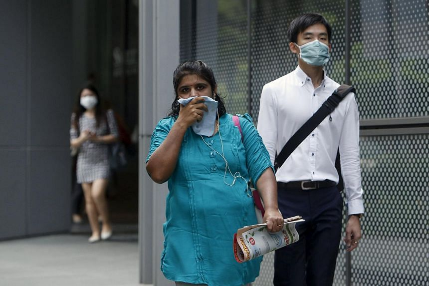 Office workers wearing masks walking in the central business district in Singapore on Sept 25, 2015.