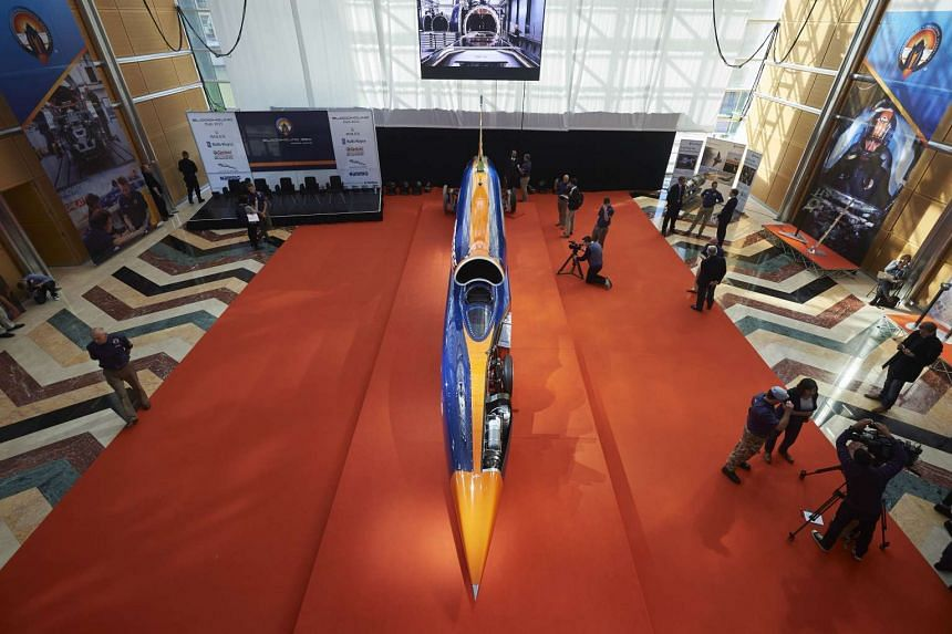 Visitors look at the Bloodhound Supersonic Car as it stands on display during a photocall to promote its World Debut, at Canary Wharf in east London on Sept 24, 2015.