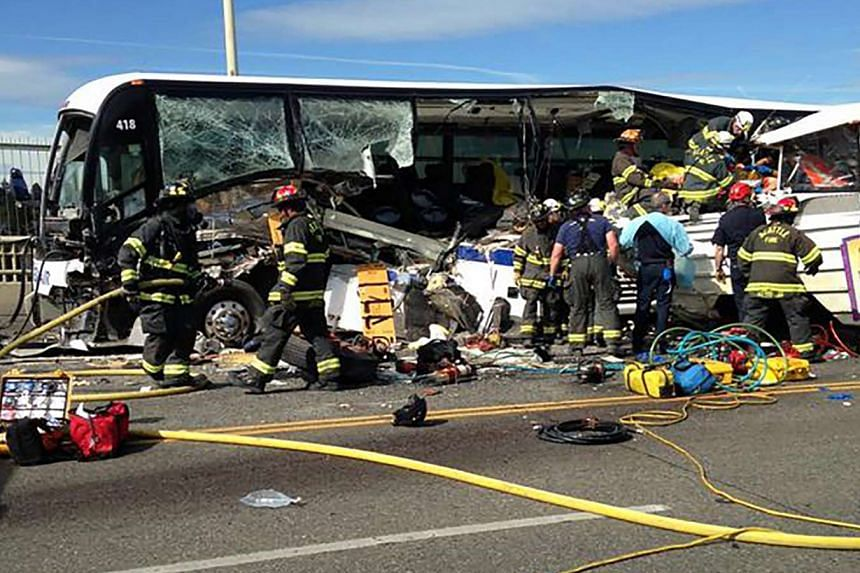 Firefighters assist victims after a crash between a bus and a tour vehicle on the Aurora Bridge in this picture from the Seattle Fire Department, in Seattle, Washington Sept 24, 2015.