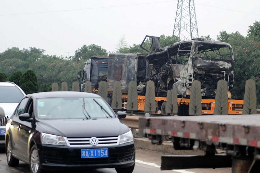 Commuters driving past the burnt-out wreckage of a bus as it is taken away after a crash with a truck near Xiangtan.