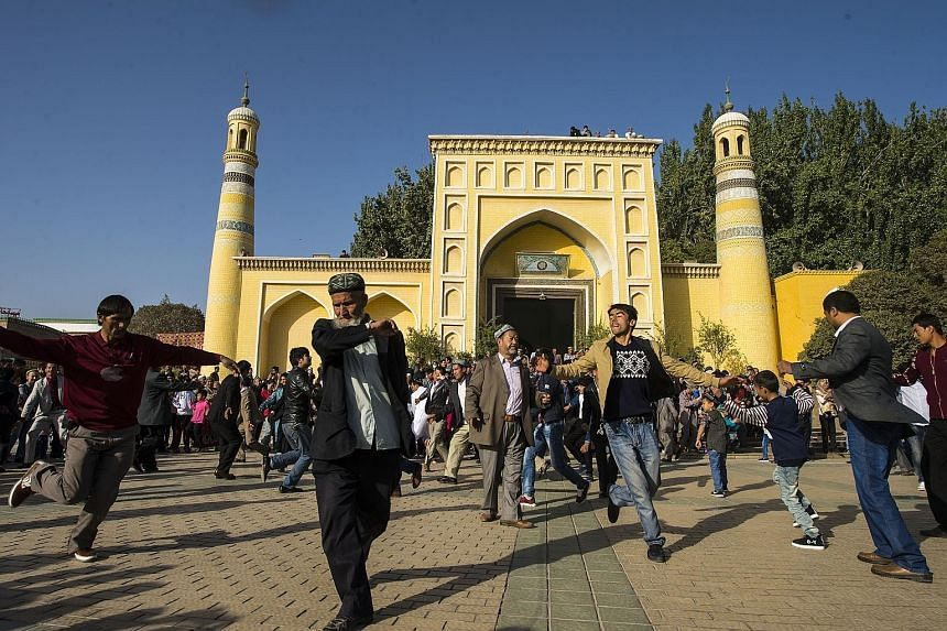 A group of Uighurs in Xinjiang doing a folk dance yesterday while celebrating Eid al-Adha in front of the Id Kah Mosque in the city of Kashgar. Critics allege that China's persecution and unfair treatment of the Muslim Uighurs, the biggest ethnic gro