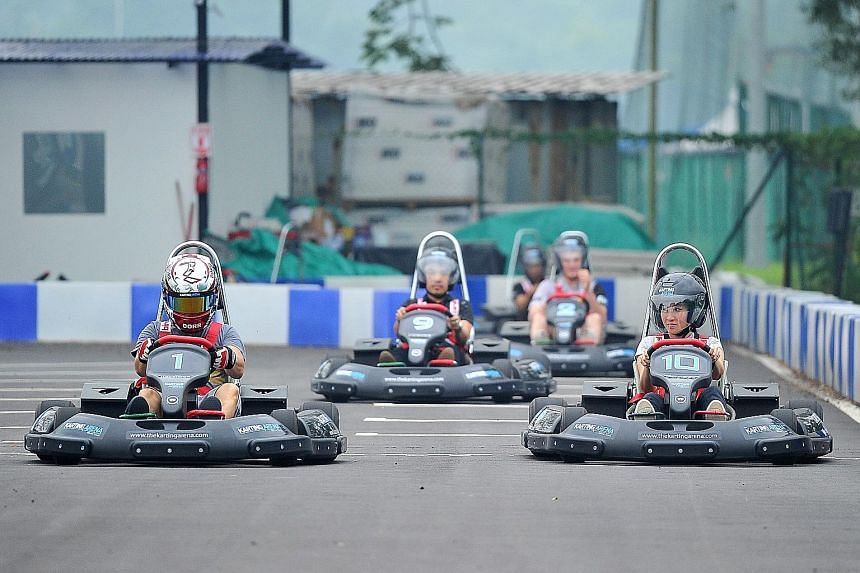 Reporter Melissa Heng (left) tries an electric go-kart. Eleven-year-olds Ollie Blakey (sitting from left) and Sam Stewart trying out the simulators. The $1.4-million electric karting circuit (above) in Turf City, Bukit Timah, has a 500m-long track wi