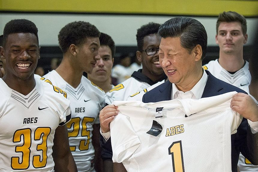 """Chinese President Xi Jinping holding a football jersey which reads """"Xi"""" on the back, given to him by players during a visit to Lincoln High School in Tacoma, Washington, on Wednesday. Mr Xi's two-day stop in Seattle presented an opportunity for him t"""