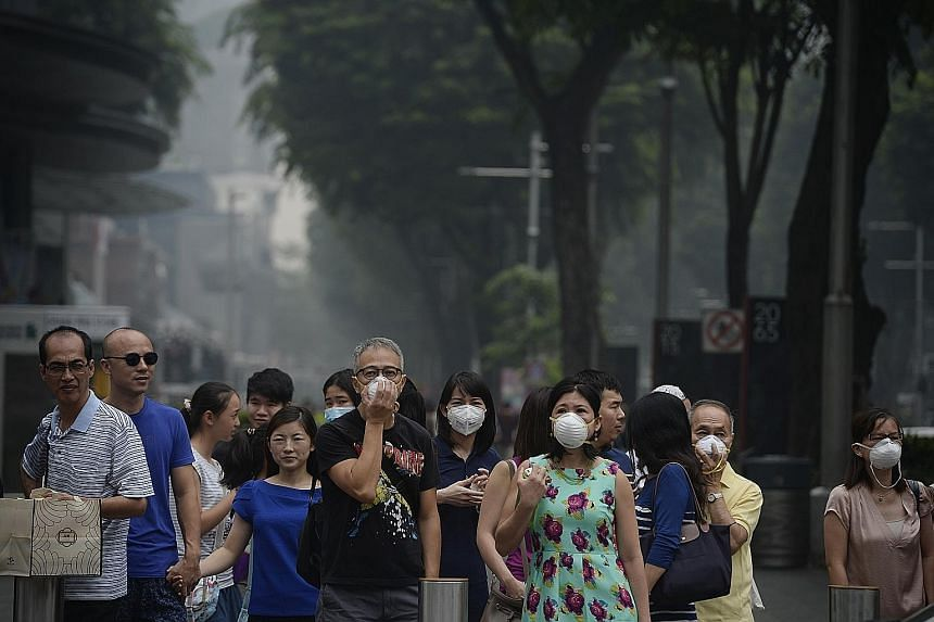 Shoppers put on masks in Orchard Road yesterday afternoon. At 10pm, the 24-hour PSI had soared to 223-275. Beyond 300, it is hazardous.