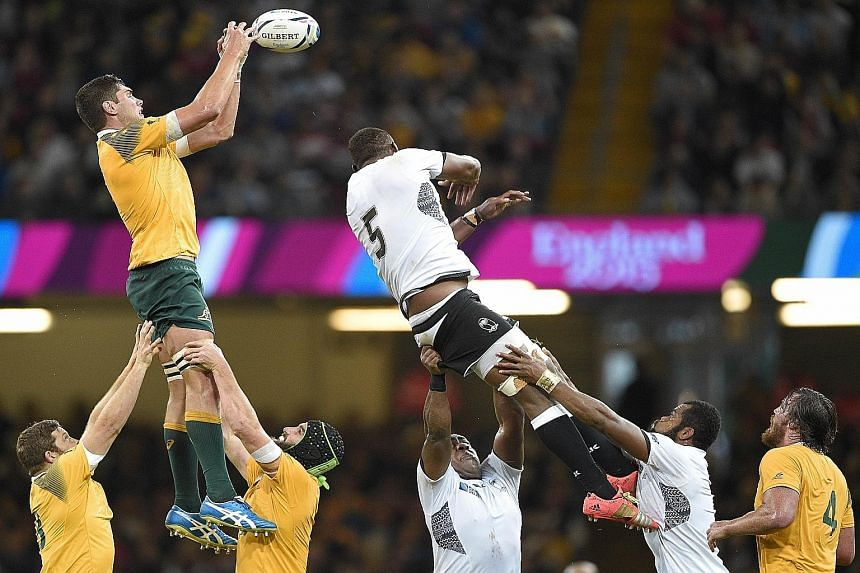 Australia's Rob Simmons (left) catching the ball in a line-out against Fiji's Leone Nakarawa (No. 5). Wallabies coach Michael Cheika has deployed a rolling maul off attacking line-outs to good effect.