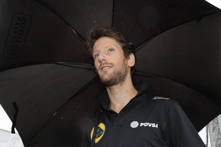 Lotus driver Romain Grosjean finding shelter under an umbrella at Suzuka. He had to conduct his press briefing out in the paddock area.
