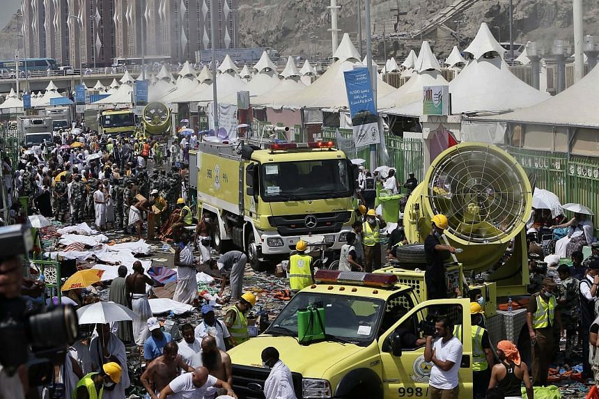 Members of the Saudi emergency services moving among the bodies of those killed in the stampede as pilgrims looked on yesterday in Mina, about 5km from Mecca. The Saudi civil defence service said more than 220 ambulances and 4,000 rescue workers had