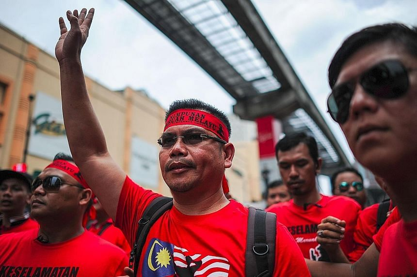 """Mr Jamal Yunos (centre), leader of the """"Himpunan Maruah Melayu"""" (Malay Dignity Uprising) rally, warned of """"another commotion"""" in Petaling Street if demands by the red-shirt protesters are not met."""