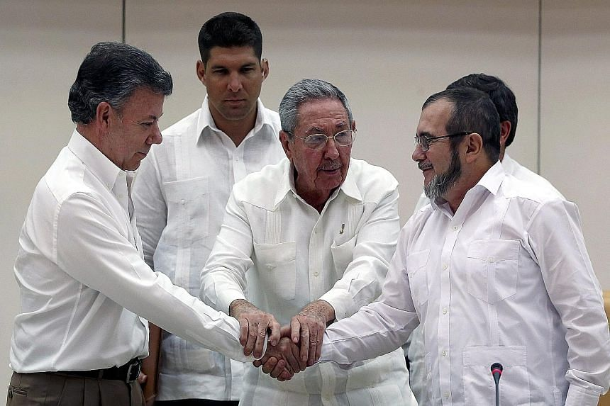 """Cuban President Raul Castro (centre) holding the hands of Colombian President Juan Manuel Santos (far left) and Farc leader Timoleon """"Timochenko"""" Jimenez during a press conference on Wednesday. The Colombian government and the rebel group reached a p"""