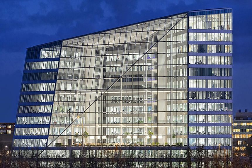 From the outside (left), the Edge building in Amsterdam looks as if a wedge has been sliced off the building. Inside (below), about 2,500 Deloitte workers share 1,000 desks, which are used only when they are needed. The building, rated the greenest i