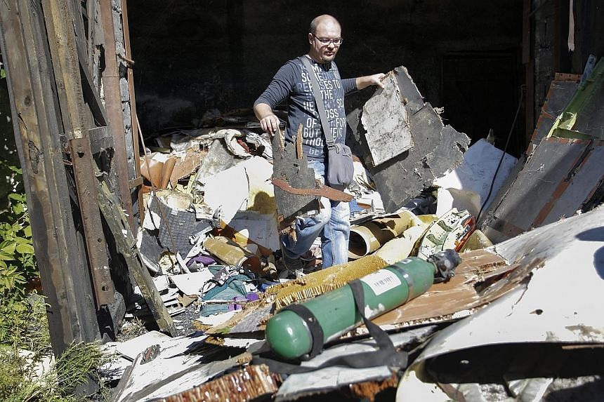 An investigator inspecting the wreckage of Flight MH17 at a village in the Donetsk area of Ukraine on Sept 16.