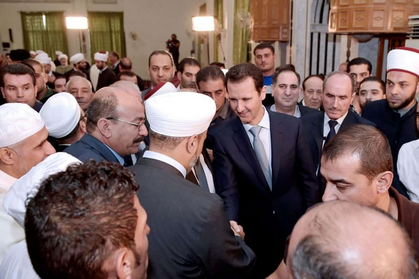 Syrian President Bashar al-Assad (centre) greeting religious figures after the morning prayer.