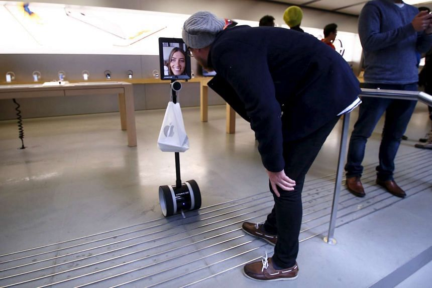 A man talks to Lucy Kelly on a screen attached to a 'telepresence robot', which she used to purchase her iPhone 6s during the official launch at the Apple store in central Sydney, Australia, Sept 25, 2015.