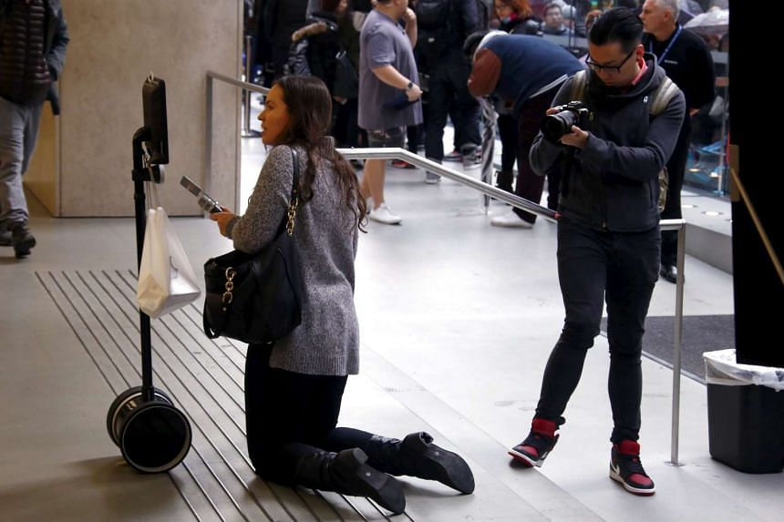 A radio journalist interviews Lucy Kelly on a screen attached to a 'telepresence robot', which Lucy Kelly used to purchase the new iPhone 6s during the official launch at the Apple store in central Sydney, Australia.
