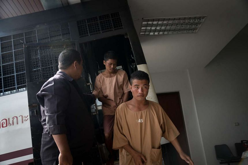 Myanmar national Zaw Lin (right) arrives in a prison transport van outside Koh Samui courthouse as fellow Myanmar national Win Zaw Tun follows on the Thai resort island of Koh Samui on Jul 9, 2015.