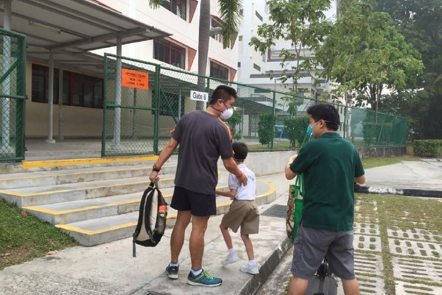 A parent sending his child to student care at Kong Hwa School.
