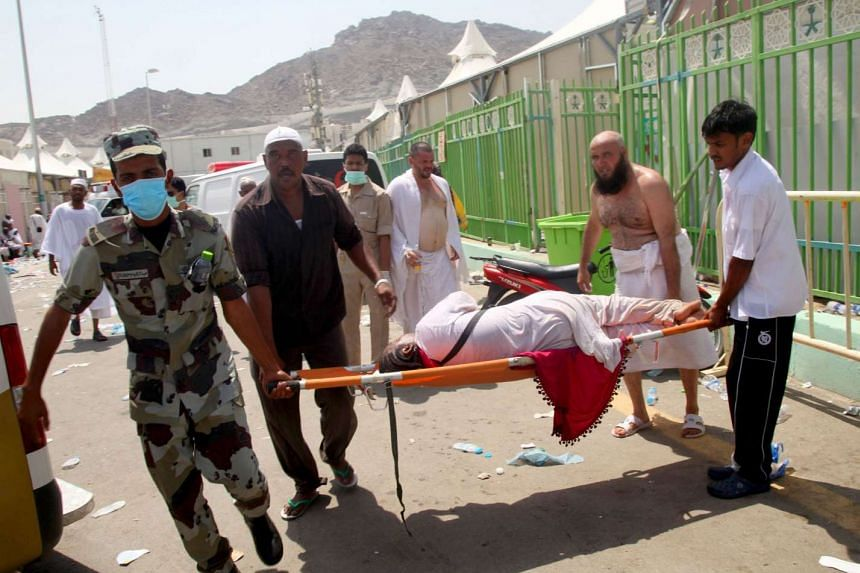 Hajj pilgrims and Saudi emergency personnel carry a woman on a stretcher.