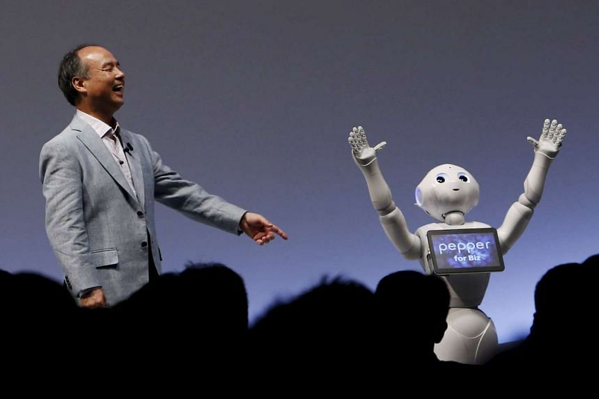 """SoftBank Group Corp. Chairman and CEO Masayoshi Son reacts as SoftBank's human-like robots named """"Pepper"""" performs during the SoftBank World 2015 event in Tokyo."""