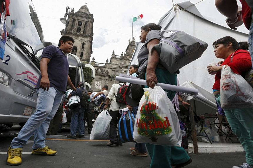 Relatives of some of the 43 missing students of Ayotzinapa College Raul Isidro Burgos carry their belongings after completing a hunger strike of 48 hours, ahead of the first anniversary of the disappearance, at Zocalo Square in downtown Mexico City o