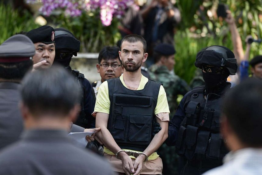 Suspect Adem Karadag is escorted by Thai commando units at a reenactment of the Bangkok bombing.