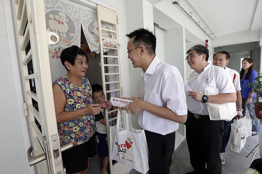Madam Chua Geok Keow, 65, and grandson Louis Lim, seven, receiving a WeCare pack from Jurong GRC MP Tan Wu Meng and grassroots volunteers in Clementi yesterday. The pack has items such as N95 masks and instant noodles.