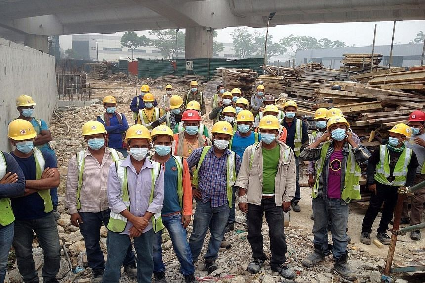 Workers at an MRT construction site in Pioneer Road wearing masks yesterday morning. Their employer, Chong Brothers General Contractor, later replaced their surgical masks with N95 masks, which offer better protection from the haze. The workers have