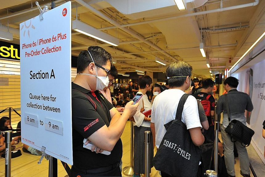 The queue outside the M1 outlet at Paragon Orchard at 7.57am yesterday. The telcos had pick-up timings.