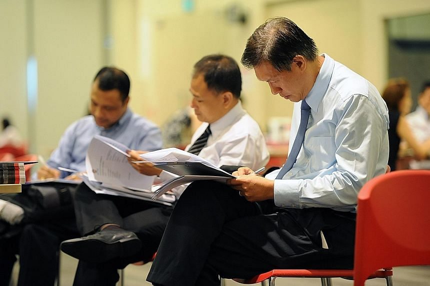 Mr Raymond Lee (at right), 49, who has been out of work for three to four months after giving up his job as a health and safety manager, was among the job-seekers at the e2i job fair for mature PMEs.