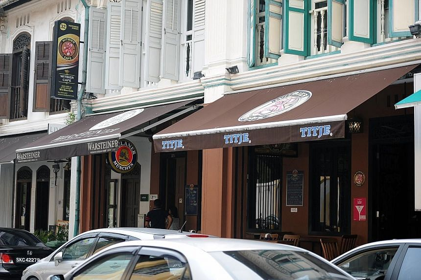 Project Lifestyle, which runs Witbier Cafe (left), was fined $35,000 yesterday for flouting a ban on bars and pubs in the Kampong Glam conservation area. It is the first such case to be prosecuted in court. The firm had ignored repeated enforcement n