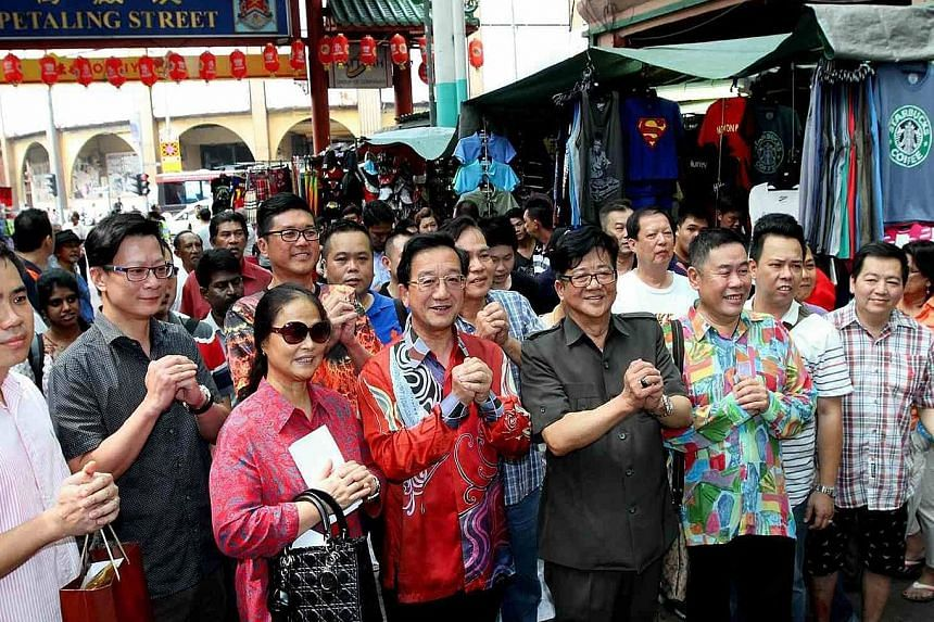Dr Huang Huikang (in red batik shirt), China's envoy to Malaysia, during his visit to Petaling Street yesterday.