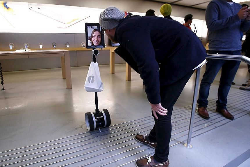 "A man talking to Ms Lucy Kelly yesterday on an iPad attached to a remote-controlled scooter. Since she was at work, she sent her ""robot"" to queue and buy the new iPhone 6s models at the Apple store in Sydney."