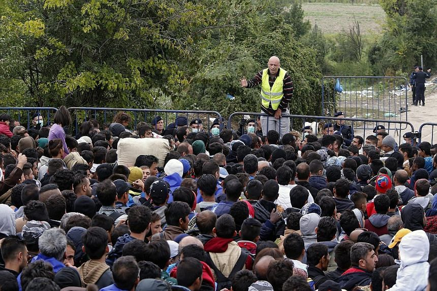 A man perched on a barrier addressing refugees waiting to enter Croatia at the border town of Berkasovo, Serbia, yesterday. The arrival of refugees in Europe, many abandoning refugee camps in Turkey, Jordan or Lebanon after three years or more, has s