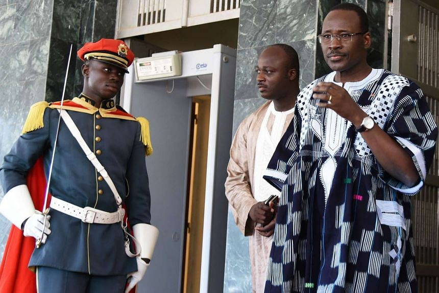 Burkina Faso's prime minister Isaac Zida (right) leaves the country's first post-coup Cabinet meeting.