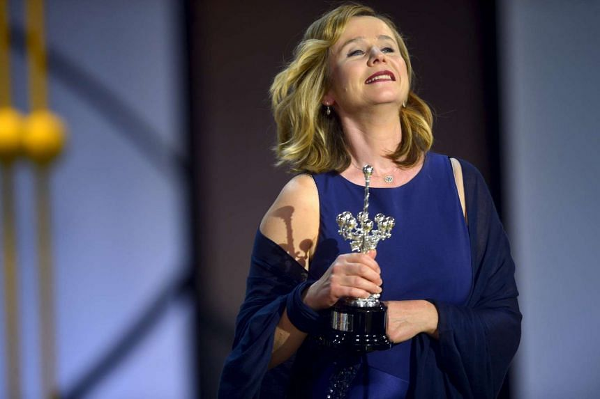 British actress Emily Watson holds up her Donostia Award for lifetime achievement.