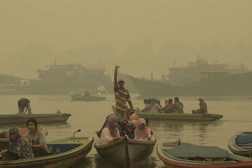 Boats carrying goods and passengers are seen on the Batang Hari River covered in a thick haze in Jambi on the Indonesian island of Sumatra on Sept 25, 2015.