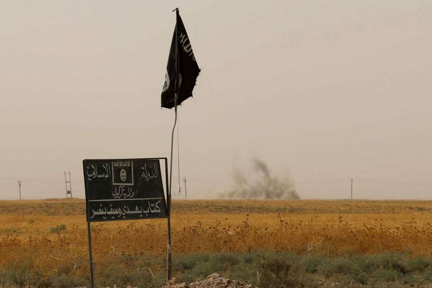 Smoke rising in the distance behind an ISIS group flag and banner on Sept 11, 2015.