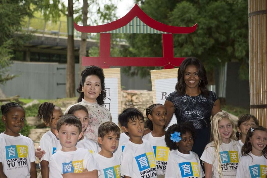 First ladies Michelle Obama and Peng Liyuan pose with students from Washington Yu Ying Public Charter School after unveiling the panda's name.