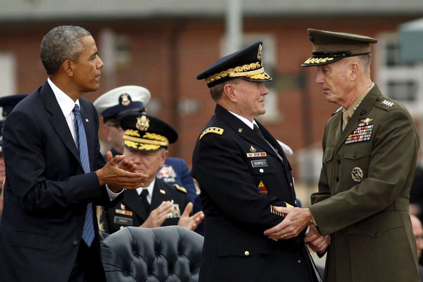 US President Barack Obama applauds as outgoing chairman of the Joint Chiefs of Staff Martin Dempsey (centre) shakes hands with his successor Marine General Joseph Dunford (right).
