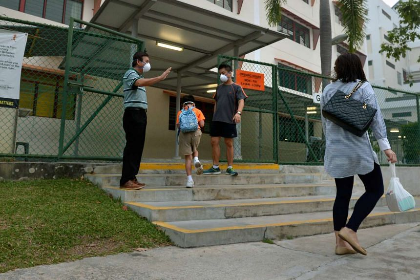A mother drops her son off at Kong Hwa School located at Guillemard Road.