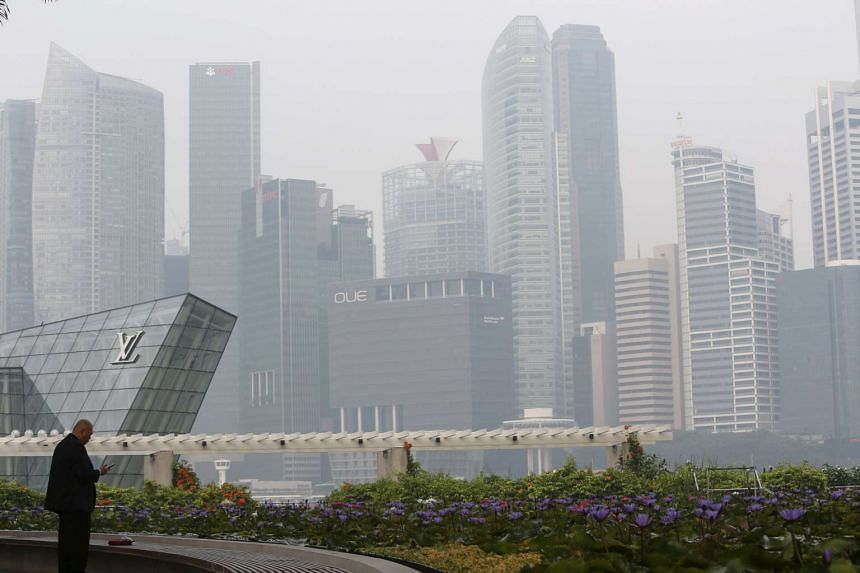 A man smokes a cigarette next to the haze-shrouded skyline in Singapore on Sept 25, 2015.