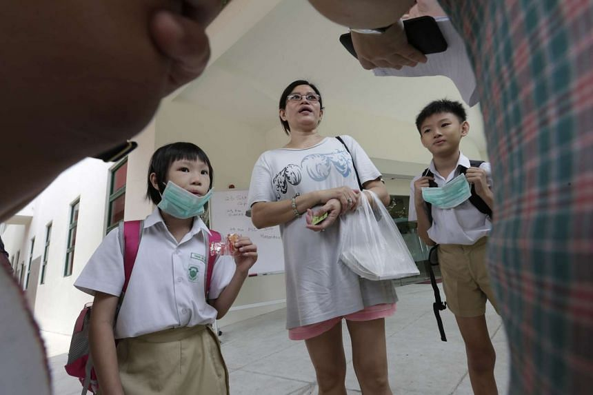 Housewife Lee Peng, 50, picking up her children Theng Wei Ern (at left), nine, and Theng Wei Zher, 10, from De La Salle School yesterday. The children were among the more than 20 pupils who showed up at the school yesterday. Some went to school so th