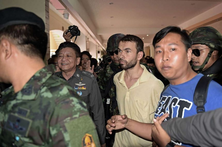 A foreign suspect in the Aug 17 Erawan shrine bombing, identified by the ruling junta as Adem Karadag (centre), is escorted by soldiers.