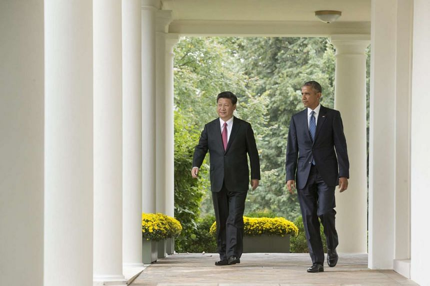 US President Barack Obama (right) and President of China Xi Jinping (left) walk down the Colonnade to hold a joint news conference in the Rose Garden of the White House, in Washington, DC, on Sept 25, 2015.