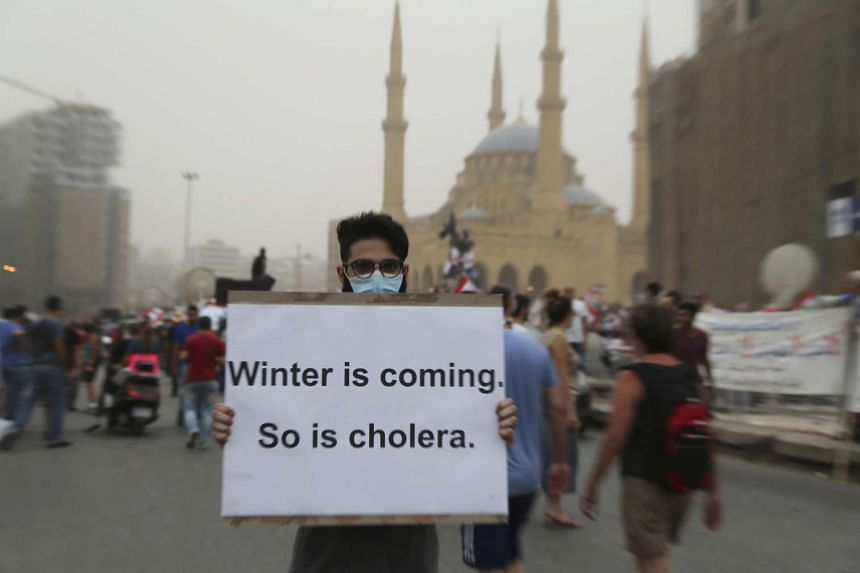 A protester wears a face mask and holds a sign during a protest against perceived government failures in downtown Beirut, Lebanon.