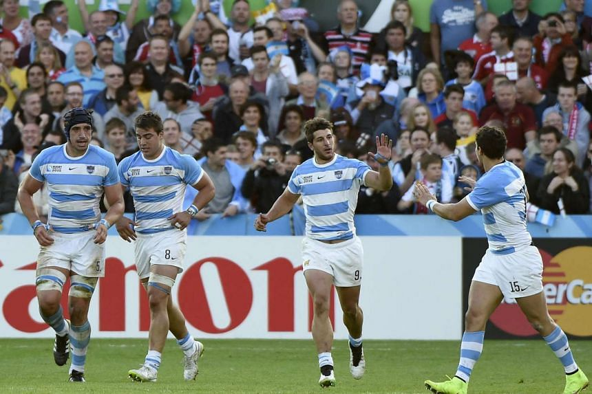 Argentina's scrum half Tomas Cubelli (centre) celebrates with teammates after scoring a try.